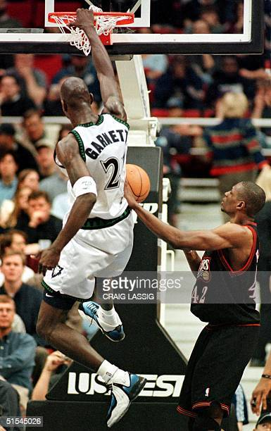 Timberwolves Kevin Garnett leaps past Philadelphia 76ers Theo Ratliff and jams the ball in the 1st quarter of their game 28 March 2000 at Target...