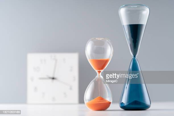 time clock and sand hourglasses - small group of objects stock pictures, royalty-free photos & images