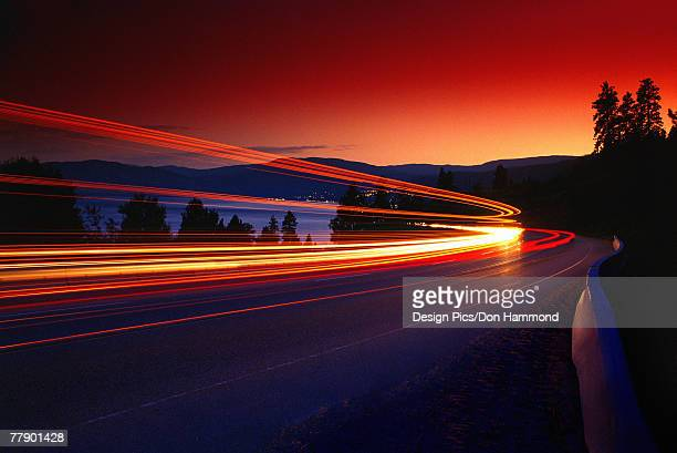 time delay of headlights on mountain road - vehicle light stock photos and pictures