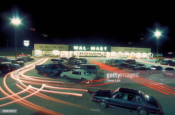 Time exposure of heavy Fri night traffic in WalMart parking lot re retailing giants' corner on discount dept store shopping market