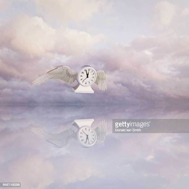 time flies: flying clock with wings - time travel stock pictures, royalty-free photos & images