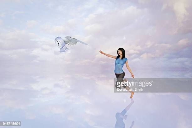 time flies: woman chasing after clock with wings, running out of time biological clock concept - time travel stock pictures, royalty-free photos & images