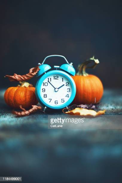 time for fall. alarm clock with leaves and pumpkins. daylight savings time. - daylight saving time stock pictures, royalty-free photos & images