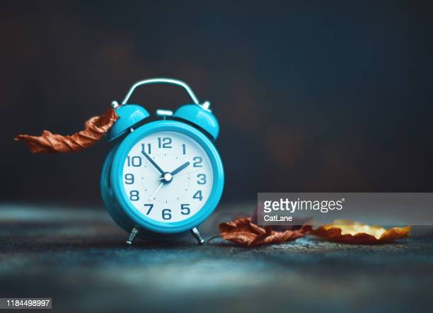time for fall. alarm clock with leaves. daylight savings time. - daylight saving time stock pictures, royalty-free photos & images