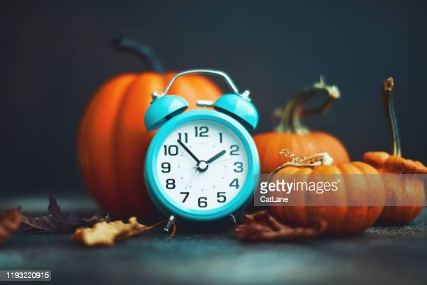 time for fall. teal alarm clock with leaves and pumpkins - daylight saving time stock pictures, royalty-free photos & images