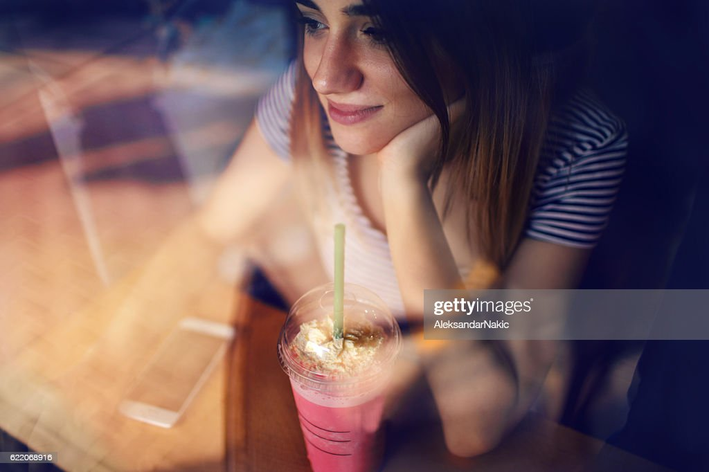 Photo of young smiling girl sitting in a cafe and using smartphone