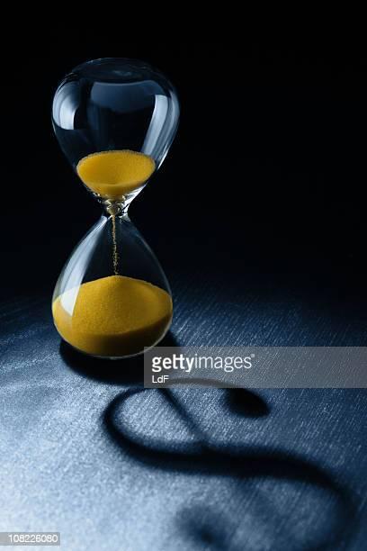 Zeit ist Geld, das Sanduhr mit Dollar-Zeichen Schatten