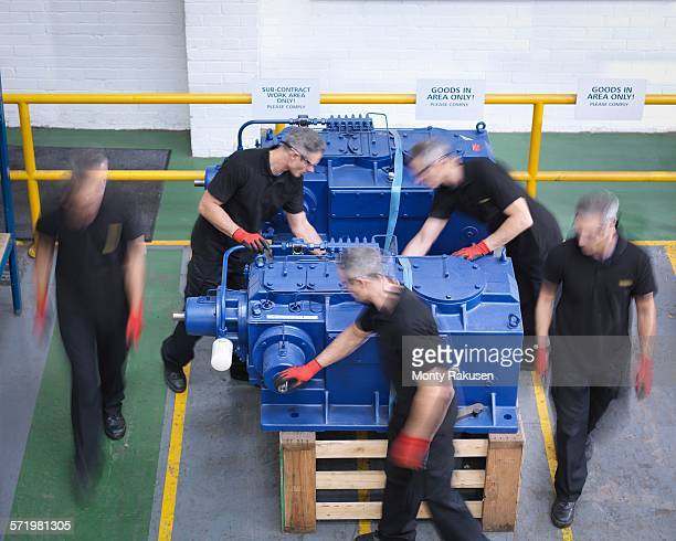 Time lapse of engineers preparing gearboxes for shipping in engineering factory