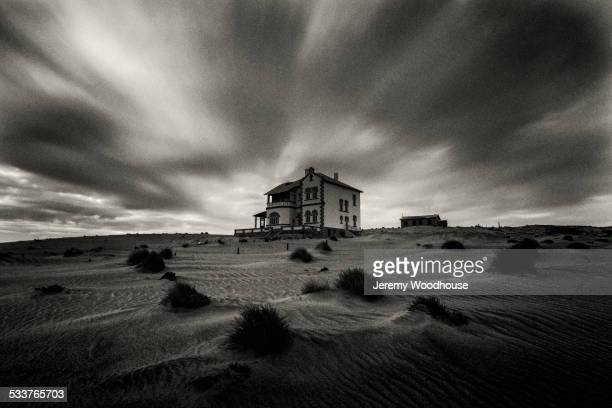 Time lapse view of dramatic clouds over house in rural landscape