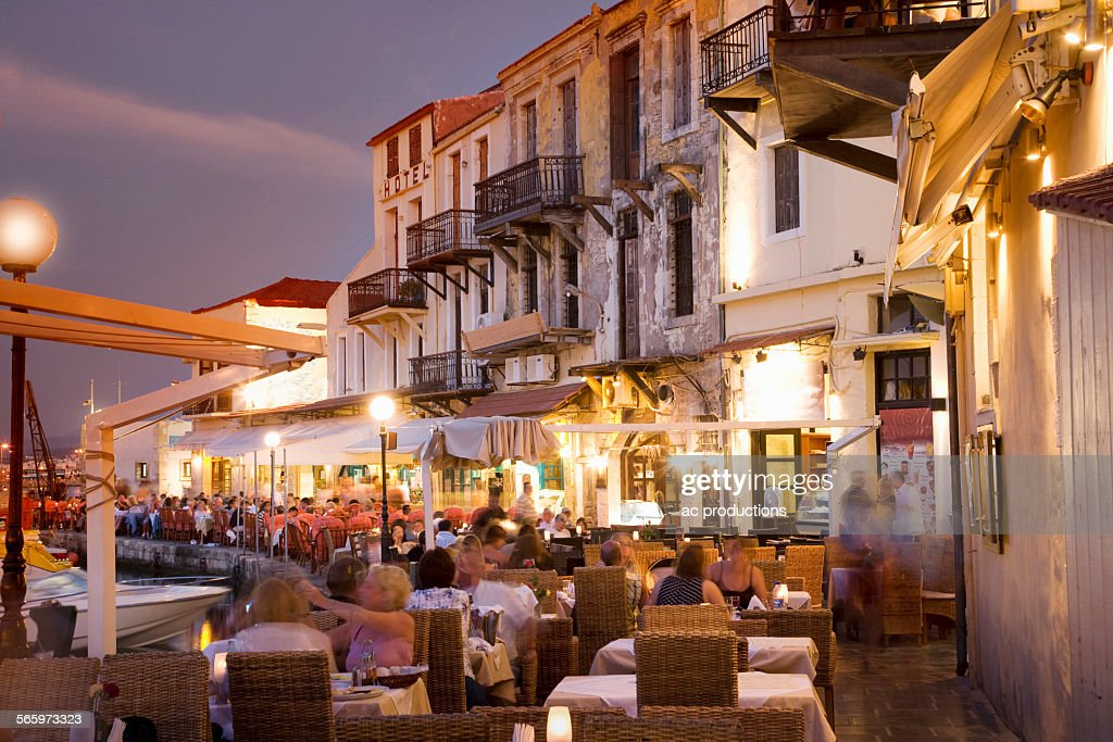Time lapse view of sidewalk cafe at sunset, Mykonos, Cyclades, Greece : Stock Photo