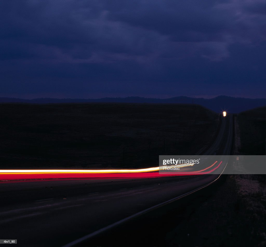 time lapsed brake lights and headlights travel on a country road to and from a mountains under a dark cloudy night : Foto de stock