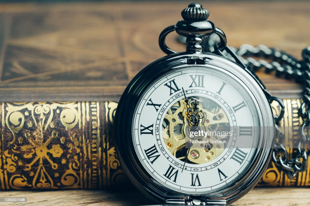 Time running, deadline, life time or business milestone concept, closed up vintage pocket watch or clock on book in vintage tone : Stock Photo