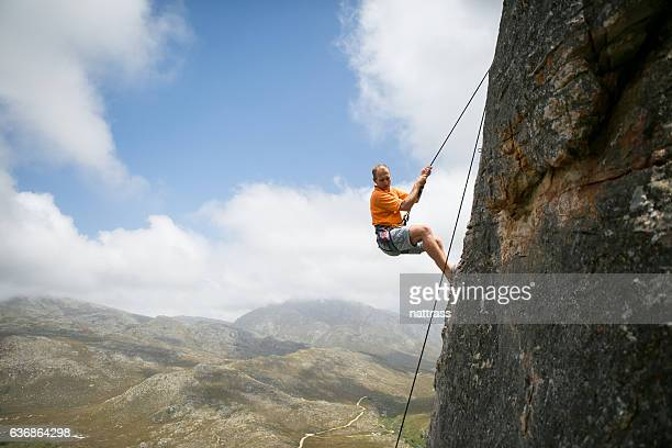 time to descent the mountain - rock overhang stock photos and pictures