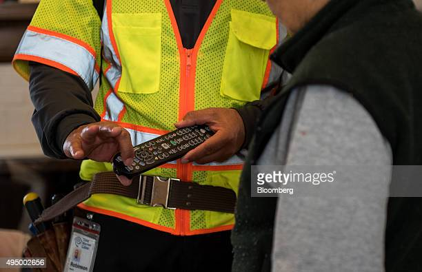A Time Warner Cable Inc technician fixes a problem with the cable inside the home of a customer in Leonia New Jersey US on Friday Oct 30 2015 Time...