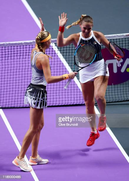 Timea Babos of Hungary and Kristina Mladenovic of France celebrate match point and advancing to the final against Samantha Stosur of Australia and...