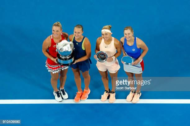 Timea Babos of Hungary and Kristina Mladenovic of France pose for a photo with the championship trophy and Elena Vesnina of Russia and Ekaterina...