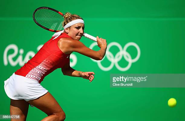 Timea Bacsinszky of Switzerland plays a backhand against Shuai Zhang of China in their first round match on Day 1 of the Rio 2016 Olympic Games at...
