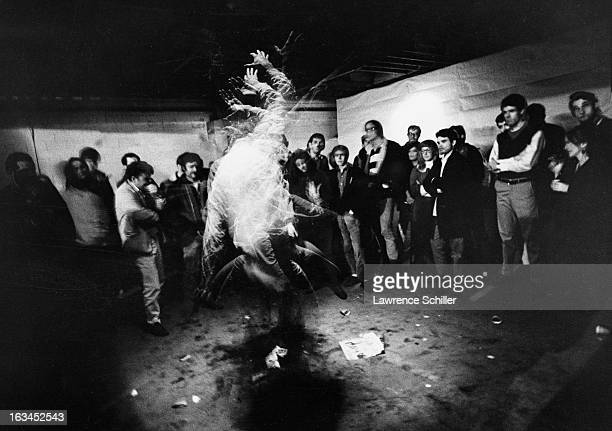 A timeexposure view of a dancer watched by onlookers under the influence of LSD at an 'Acid Test' Los Angeles California 1966 The 'Acid Tests' were...