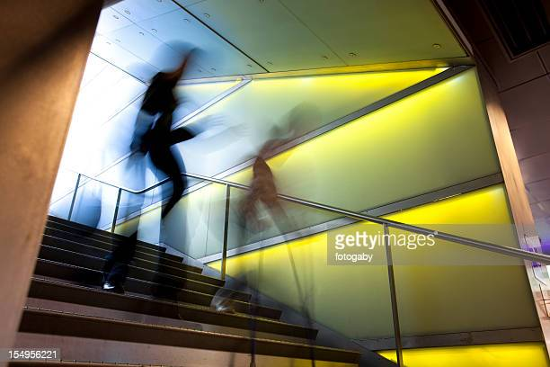 Time-lapse of two blurry people walking down stairs