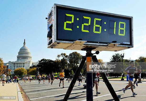 A timer on Maryland avenue keeps them up to date as runners pass by the US Capitol as they compete in the annual Marine Corps Marathon through the...