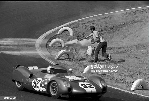 Times Grand Prix Riverside Richie Ginther of Shelby American racing drives his Ford powered Cooper King Cobra A Corner worker throws out some a...