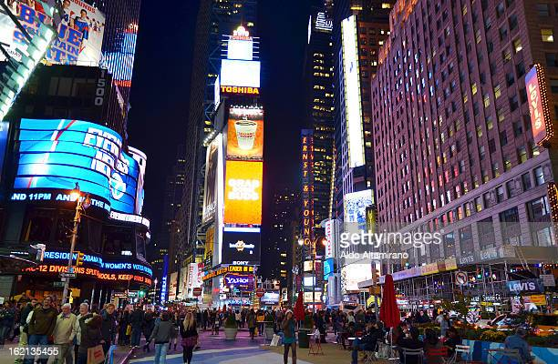 CONTENT] Times Square 7th Avenue at night People walking talking sitting looking tourist tourists person human sign signs advertising street...