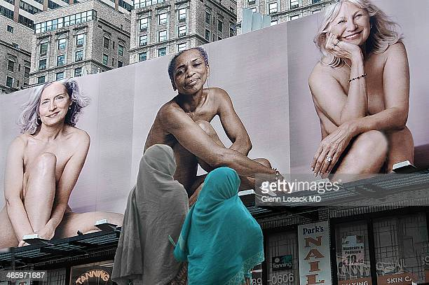 CONTENT] A times square billboard of 3 Western nude women being viewed by 2 veiled women Times Square Manhattan USA