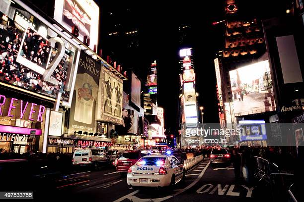 Times Square by night New York City. You can see a police car and the crowd.