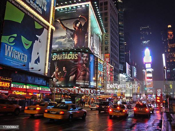 Times Square in New York City at night with many of its characteristics, like advertisements and yellow cabs.