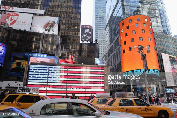 times square nyc taxi cabs and us flag nasdaq - nasdaq stock pictures, royalty-free photos & images