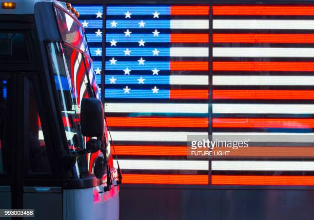 Times Square, traffic passing neon American Flag, New York City, New York, USA, North America