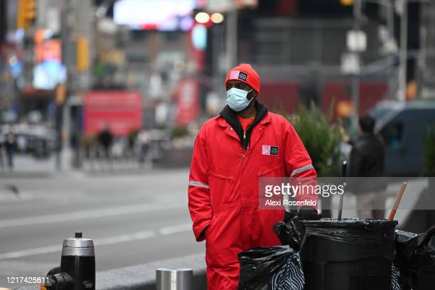 Times Square workman wearing a protective mask wheels a trashcan through an empty Times Square amid the coronavirus pandemic on April 05 2020 in New...