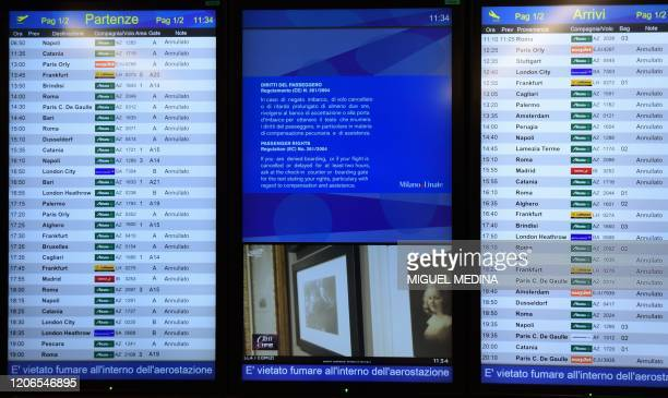 Timetable displays cancelled flights at Milan's Linate airport on March 11 a day after Italy imposed unprecedented national restrictions on its 60...