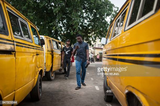 Timi Ajiboye a 23yearold software developer walks between taxis at the University of Lagos while using the Pokemon Go application on his mobile on...