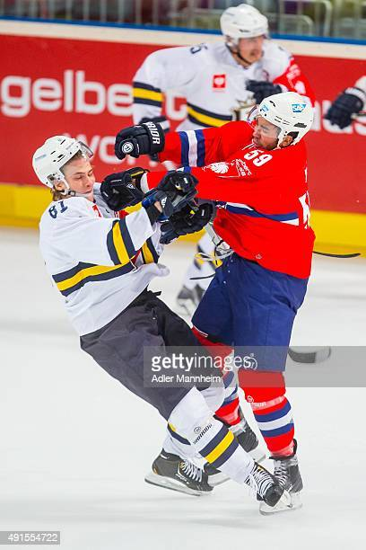 Timi Lahtinen of Espoo Blues clashes with Brandon Yip of Adler Mannheim during the Champions Hockey League round of thirty-two game between Adler...