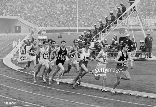 Timing judges watch as Alan Simpson , Dyrol Burleson , Witold Baran , John Whetton , John Davies and eventual winner Peter Snell of New Zealand...