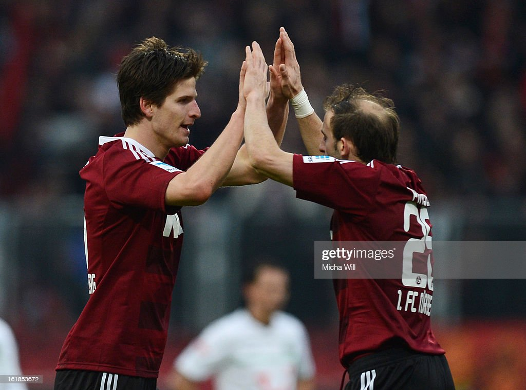 Timm Klose (L) of Nuernberg celebrates with team-mate Javier Pinola after scoring their team's first goal to equalise during the Bundesliga match between 1. FC Nuernberg and Hannover 96 at Grundig-Stadion on February 17, 2013 in Nuremberg, Germany.