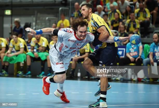 Timm Schneider of Melsungen is challenged by Alexander Petersson of RheinNeckar Loewen during the DKB HBL match between RheinNeckar Loewen and MT...