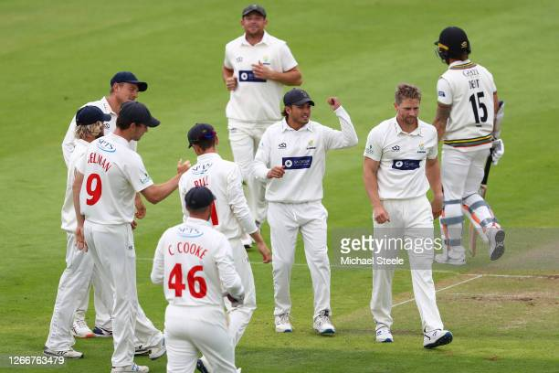 Timm van der Gugten of Glamorgan is congratulated by Kiran Carlson after capturing the wicket of Gloucestershire's Chris Dent during day three of the...