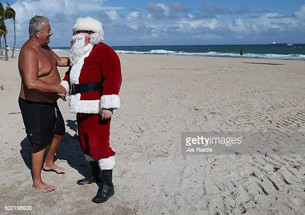 Timmy McGovern dressed as Santa Claus greets Michel Talbot as he walks along the beach passing out candy canes and posing for pictures with beach...