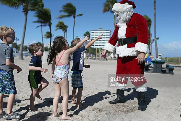 Timmy McGovern dressed as Santa Claus walks along the beach passing out candy canes and posing for pictures with beach goers on December 21 2015 in...