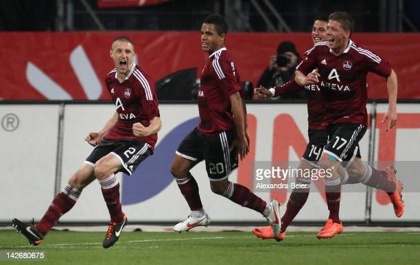 Timmy Simons of Nuernberg and his teammates Daniel Didavi, Robert Mak and Mike Frantz celebrate Simons' penalty goal during the Bundesliga match...