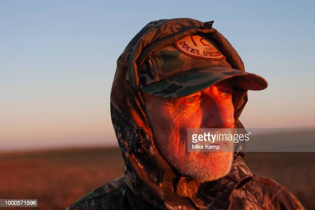 Timmy Stein duck hunting at dawn hunkered down for camouflage on a hilltop southeast of Minot North Dakota United States The duck hunters travel in...