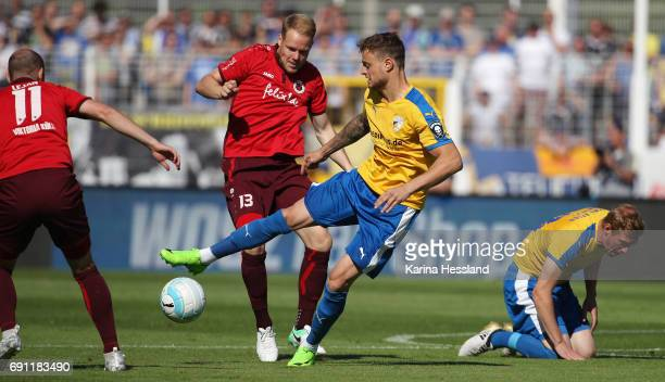 Timmy Thiele of Jena challenges Lukas Nottbeck of Koeln during the Third League Playoff Leg Two between FC Carl Zeiss Jena and Viktoria Koeln on June...