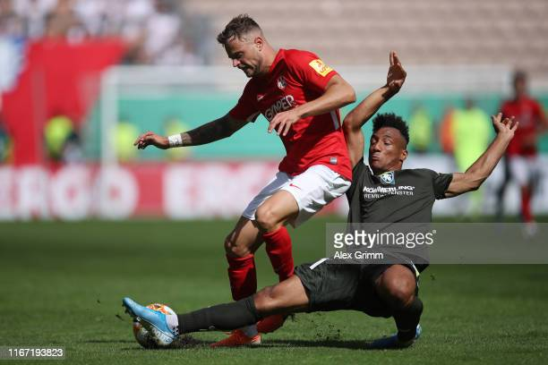 Timmy Thiele of Kaiserslautern is challenged by Karim Onisiwo of Mainz during the DFB Cup first round match between 1 FC Kaiserslautern and 1 FSV...