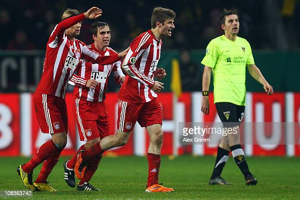 Timo Achenbachen of Aachen reacts as Thomas Mueller of Muenchen celebrates his team's third goal with team mates Philipp Lahm and Anatoliy Tymoshchuk...