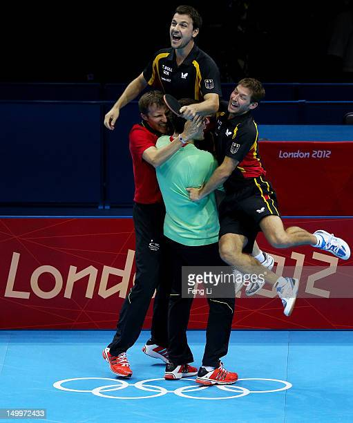 Timo Boll of Germany and team celebrate Boll defeating Tianyi Jiang of Hong Kong, China and winning the Men's Team Table Tennis bronze medal match on...