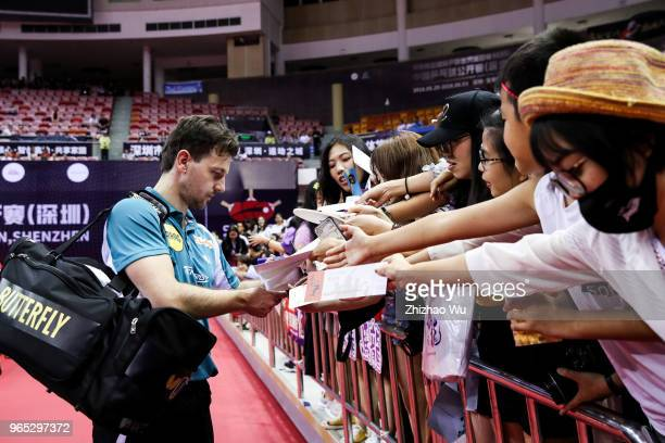 Timo Boll of Germany signs for the crowd after the men's singles match Round of 16 compete with Liang Jingkun of China during the 2018 ITTF World...