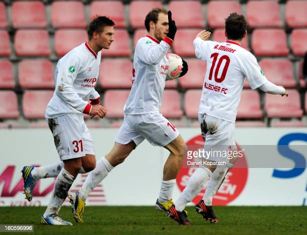 Timo Furuholm of Halle celebrates his team's first goal with team mates Kristian Kojola and Anton Mueller during the third Bundesliga match between...
