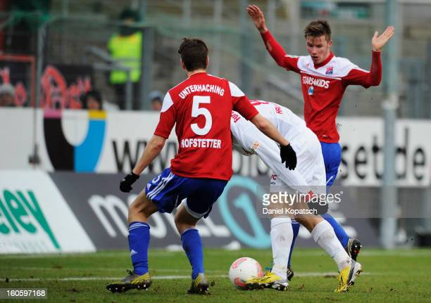 Timo Furuholm of Halle scores his team's first goal next to Daniel Hofstetter and Maximilian Drum of Unterhaching during the third Bundesliga match...